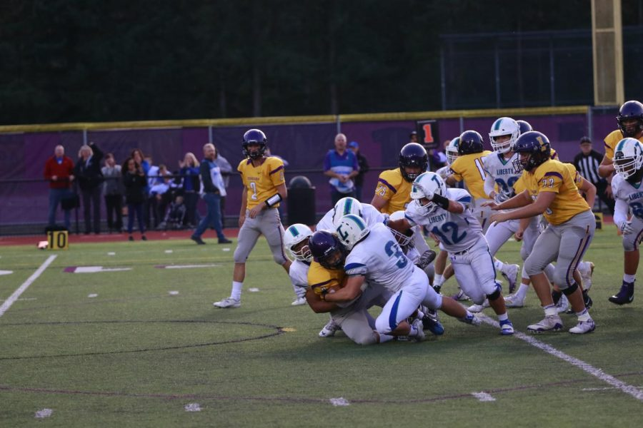 CAREFUL OF CONCUSSIONS! Issaquah's running back is tackled to the ground by three Liberty defenders in a low-scoring 9-3 loss for Issaquah. Research shows that the repeated blows to one's head may lead to them developing harmful brain diseases later in their life.