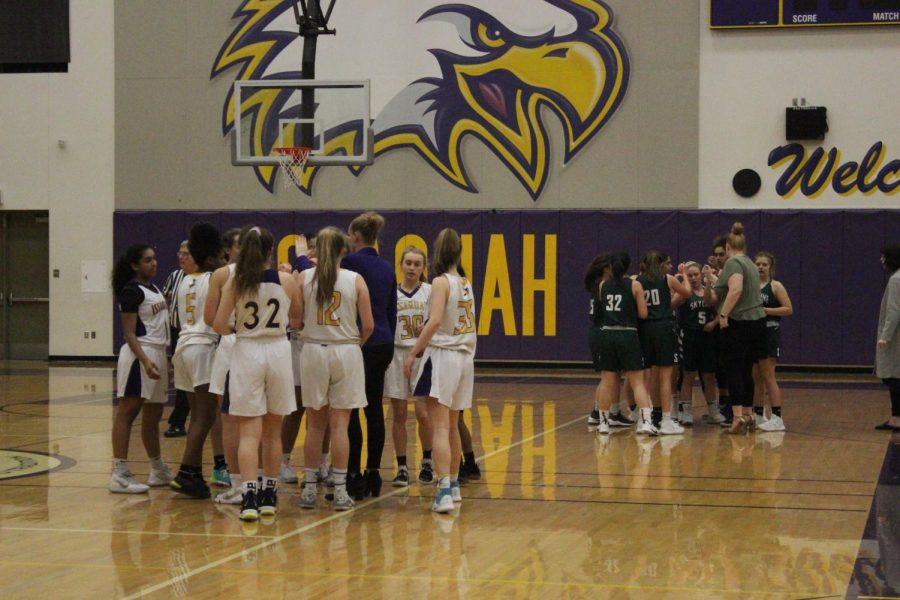 GEARING UP: The Issaquah and Skyline girls teams huddle up and discuss improvement strategies with their coaches.
